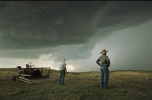 A thunderstorm halts haying as two farmers watch the sky. Nebraska, 2004. Photo by Jim Richardson/National Geographic Stock