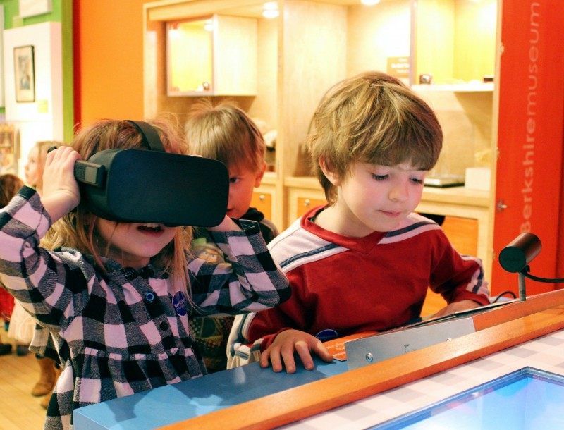 Two children, one wearing a virtual reality headset.