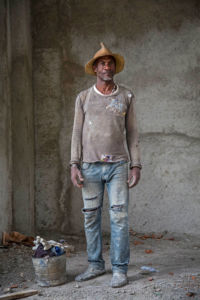 A dark-skinned man in paint-stained, ripped clothes and a hat stands in a grey space