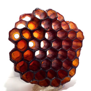 3D amber-colored honeycomb set on a white background